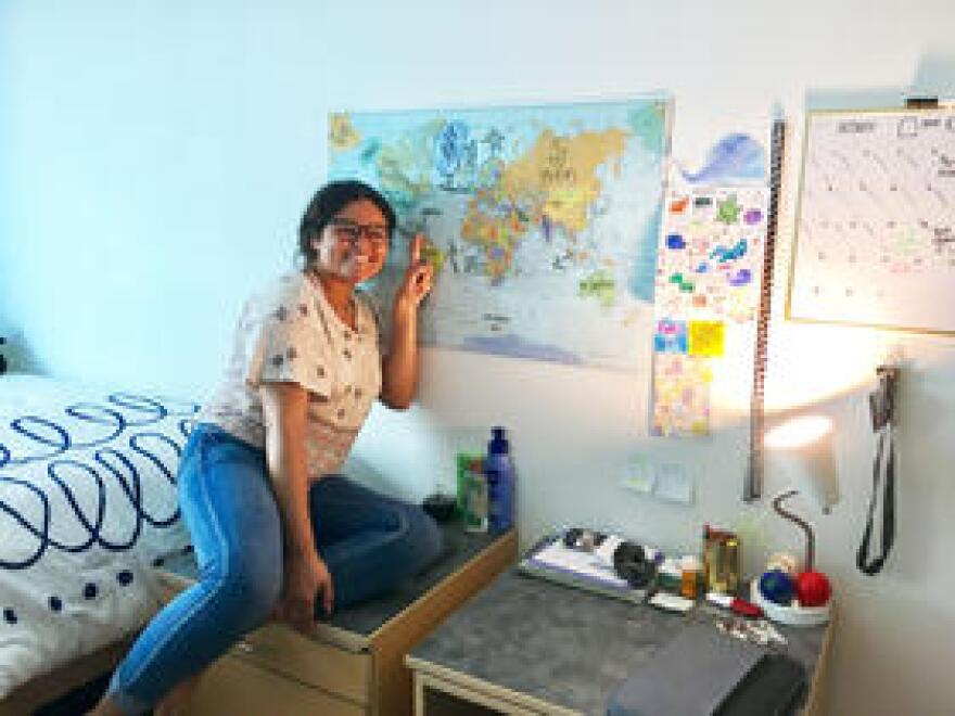 "Florida Atlantic University student Ana Escobar points at Puerto Rico on a world map in her dorm room. She circled the island and wrote ""home"" with a heart."