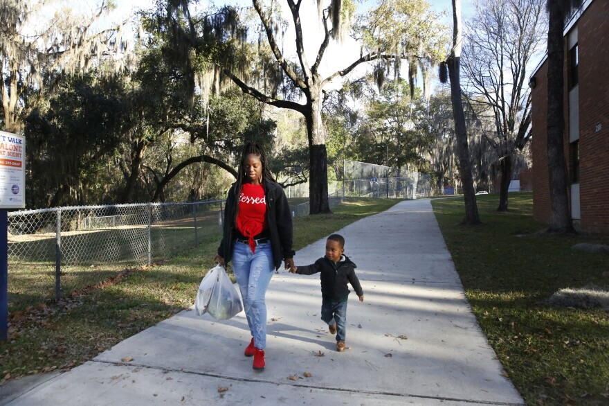 Akiya Parks, a senior at the University of Florida, and her 3-year-old son Caleb, walk through campus.