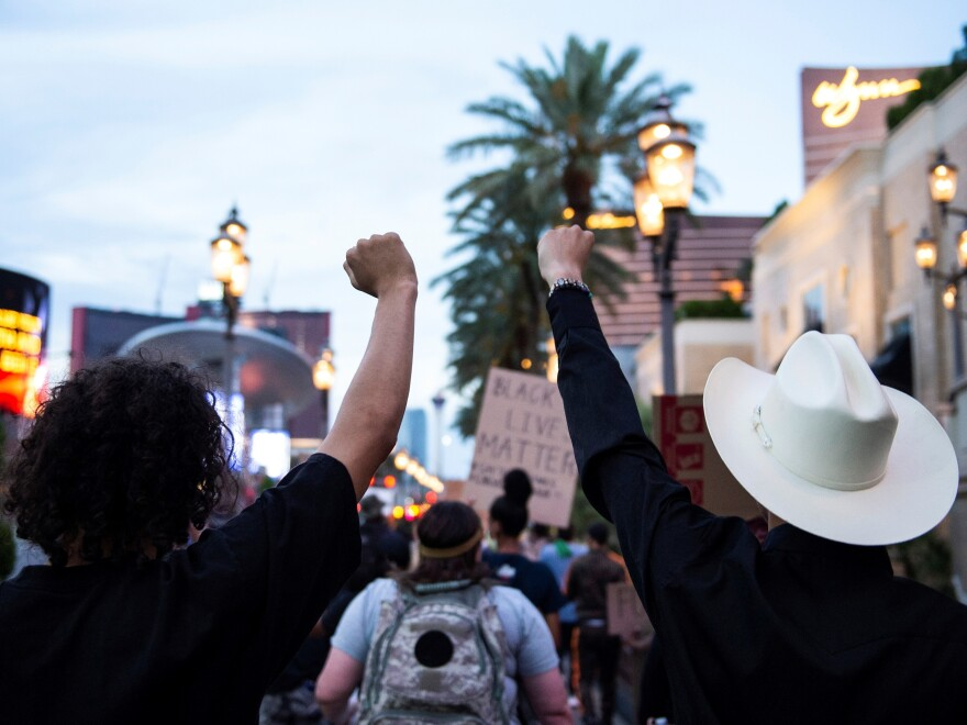 Protesters shout slogans and hold placards on Monday in downtown Las Vegas as they take part in a Black Lives Matter rally.
