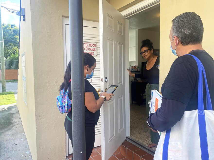 In their canvassing of a predominantly Cuban American neighborhood in October, Díaz (right) and another community outreach worker, María Elena González (left), spoke with Gloria Carvajal about how to get a COVID-19 test.