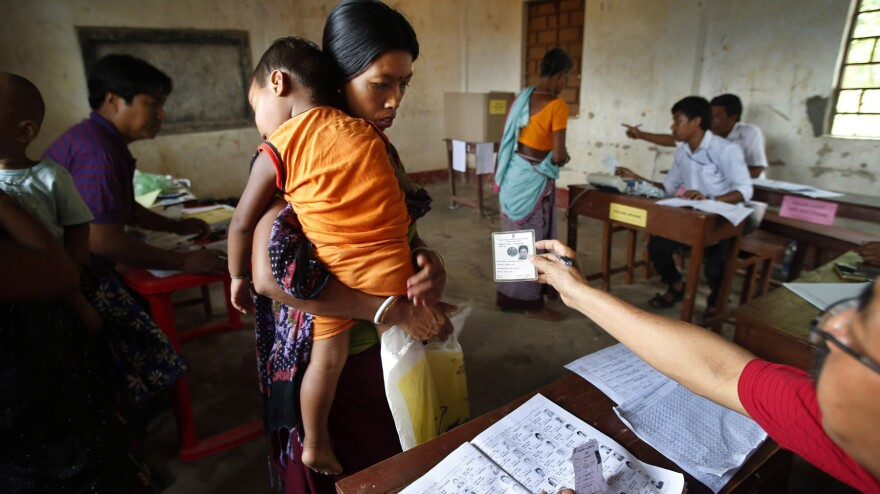 A woman in the northeastern Indian state of Tripura receives her identity card back from an election official on Monday. India began six weeks of voting in a country where more than 800 million are registered to cast ballots.