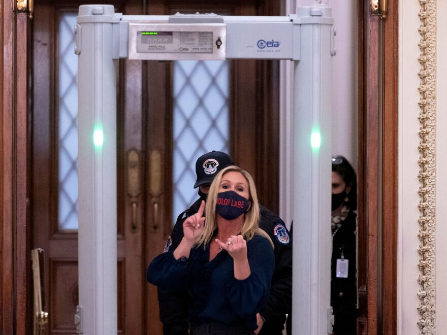Republican Rep. Marjorie Taylor Greene of Georgia shouts at journalists as she goes through security outside the House Chamber at Capitol Hill.
