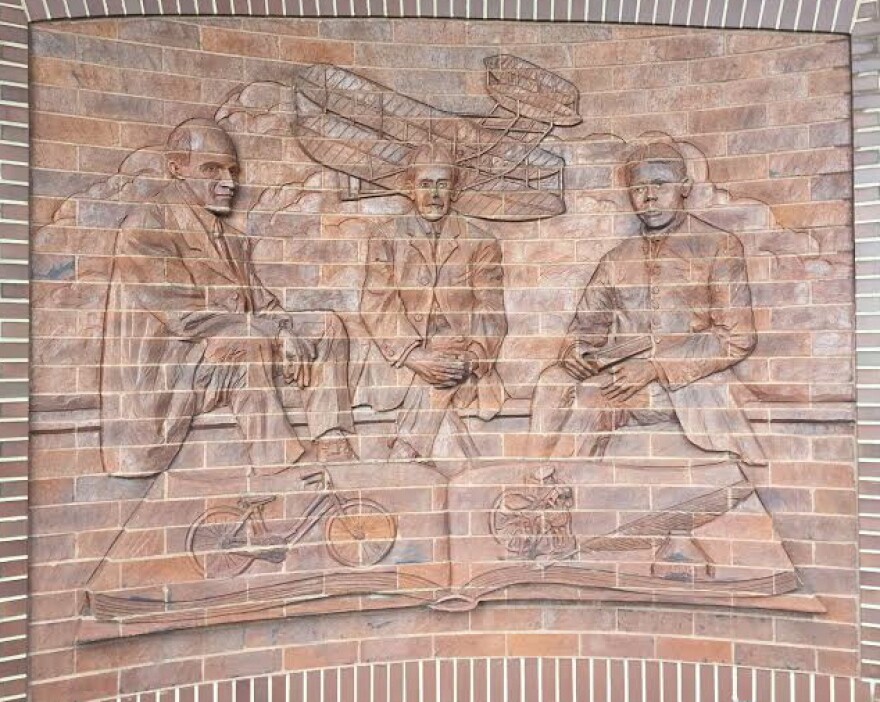 The masonry outside the Wright Dunbar Interpretive Center depicts Dunbar sitting next to his friends, Orville and Wilbur Wright.