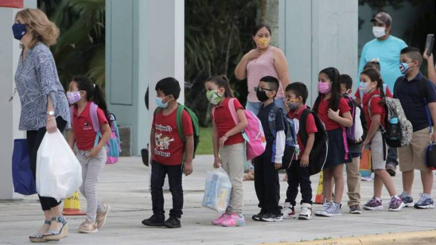 First graders at Redland Elementary in Homestead are led into the classroom by their teacher after being dropped off by their parents on Oct. 5. It was the first day of Miami-Dade County Public Schools opened for in-person classes since the onset of the pandemic.