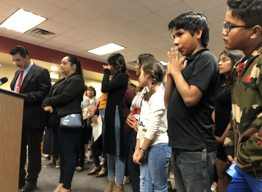 Community organizers with the COPS/Metro Alliance speaks to the Southside school board Oct. 17, 2019 as a mom who was denied access to her son's school wipes away a tear.
