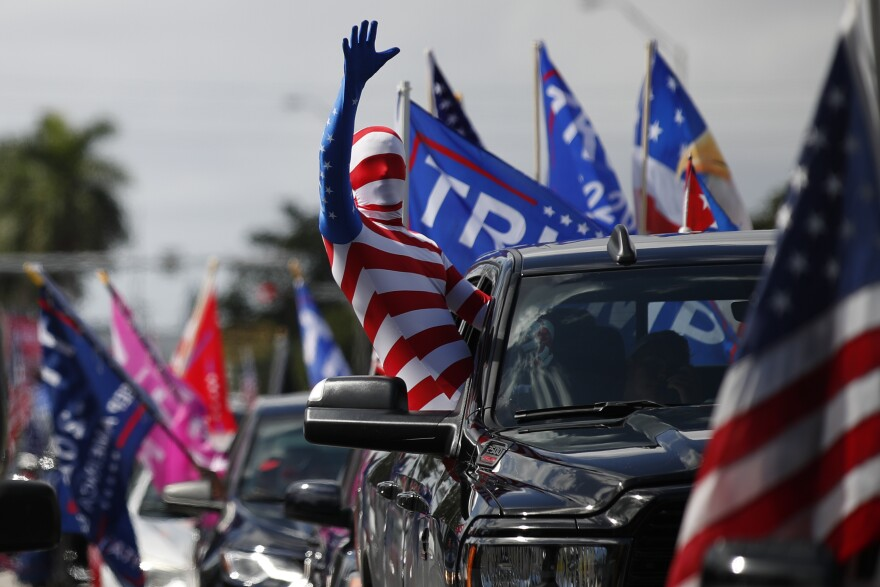 A man wearing a flag-themed body stocking waves from a car as hundreds of vehicles gather at Tropical Park ahead of a car caravan in support of President Donald Trump, in Miami, Sunday, Nov. 1, 2020.(AP Photo/Rebecca Blackwell)