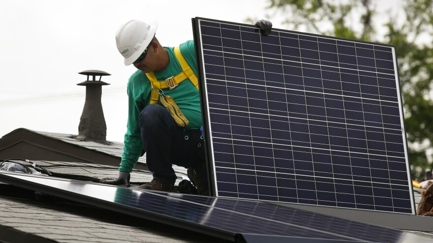 A SolarCity employee installs a solar panel on the roof of a home in Los Angeles in 2014. California's utilities want to pay new solar customers less for their extra electricity and to add new monthly fees.
