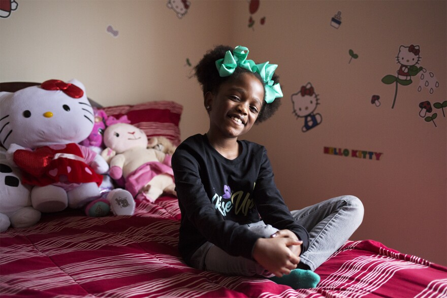 Mikaylah Norfolk poses for a portrait in her Hello Kitty-themed bedroom.