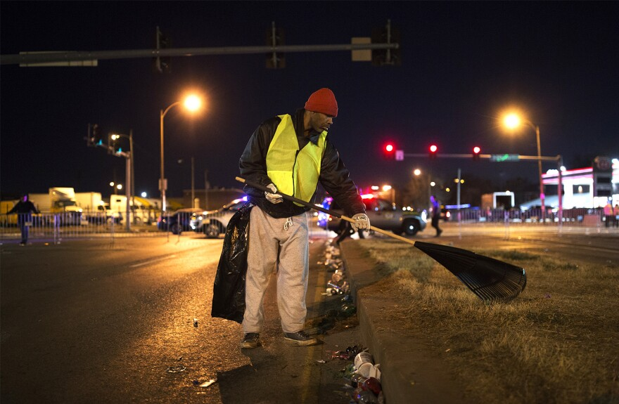 Donald Brewer starts raking trash on 7th Boulevard just after sunset on Saturday, Feb. 27, 2017.