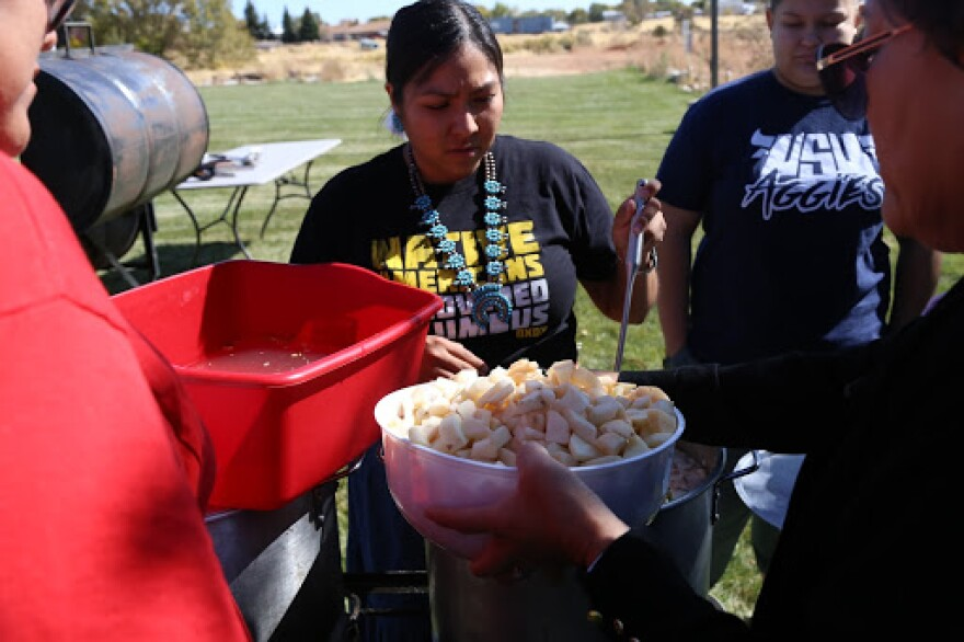 A photo of a woman wearing a traditional Navajo squash blossom necklace stirring a pot with a ladle as potatoes are added.