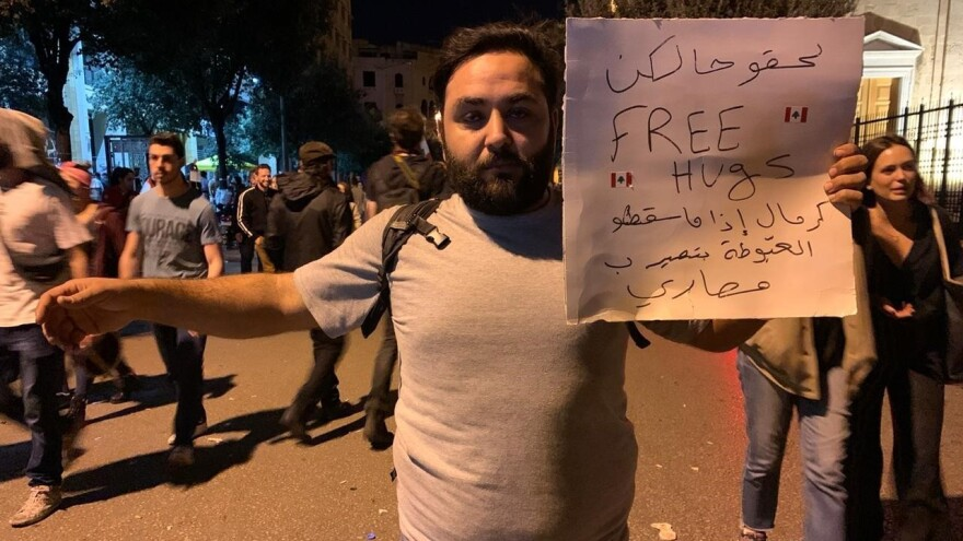 "Mahmoud Aswany holds a sign in Beirut that reads, ""Hurry up free hugs"" — a dig at the government's attempts to raise revenue from taxes."