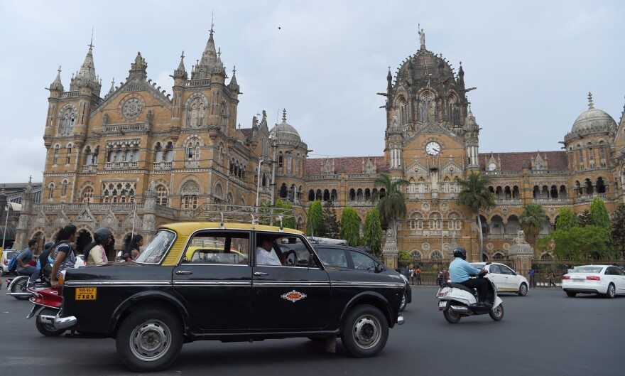 An Indian taxi driver drives his Premier Padmini past the iconic building Chhatrapati Shivaji Terminus railway station in Mumbai, India.