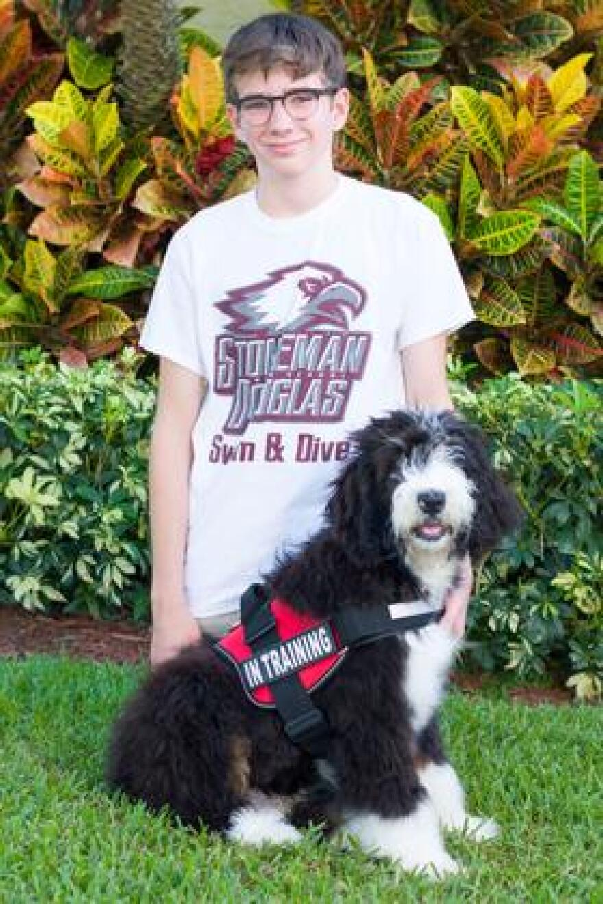 William Olson on the day he received his donated therapy dog, Skipper. Skipper is a cross between a Bernese Mountain Dog and a poodle.