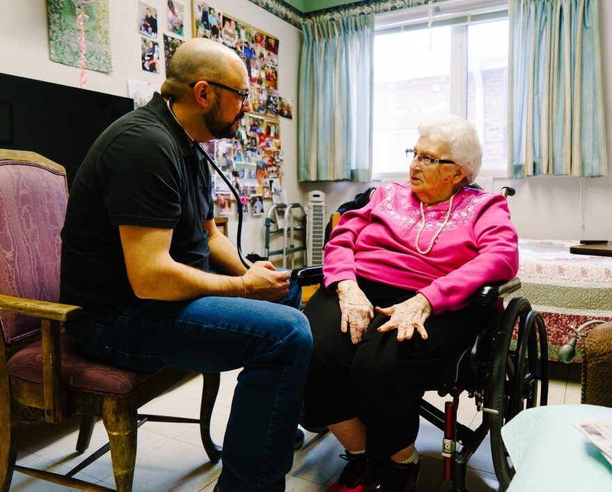 Glenn Hurst gives Jeannette Massen a checkup at the Northcrest Living Center in Council Bluffs, Iowa. As they prepare to caucus, voters weigh which candidate to support and what health care should look like in the future.