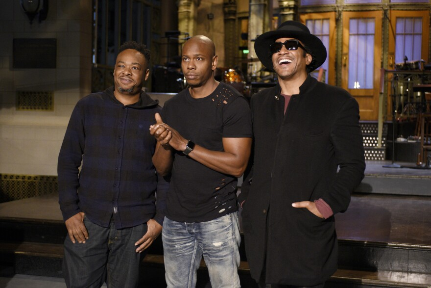 Jarobi White (left) and Q-Tip (right) of musical guest A Tribe Called Quest pose with host Dave Chappelle (center) on Saturday.