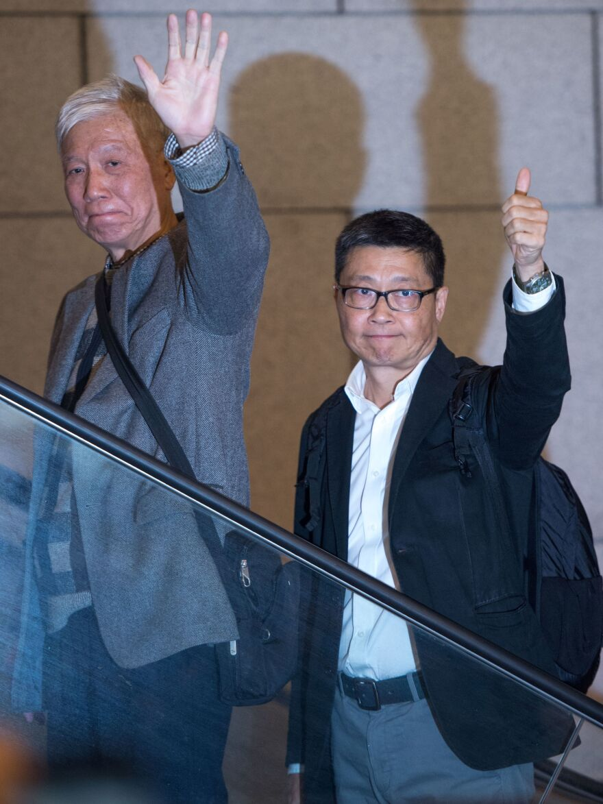 Activists Chu Yiu-ming, left, and Chan Kin-man gesture to supporters as they report to be arrested at a police station in Hong Kong. Police say the men and other Umbrella Movement activists will be charged over mass protests that took place in 2014.