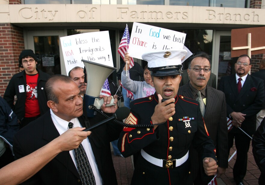 Former Marine Sgt. Salvadaor Parada, right, speaks to protesters during a rally outside city hall in Farmers Branch, Texas in 2006.
