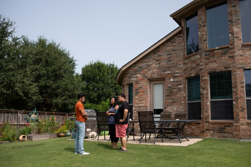 Izcan & his parents stand near a stone patio with table set and grill against the back of their brick house in their fenced yard with their white dog in the background.