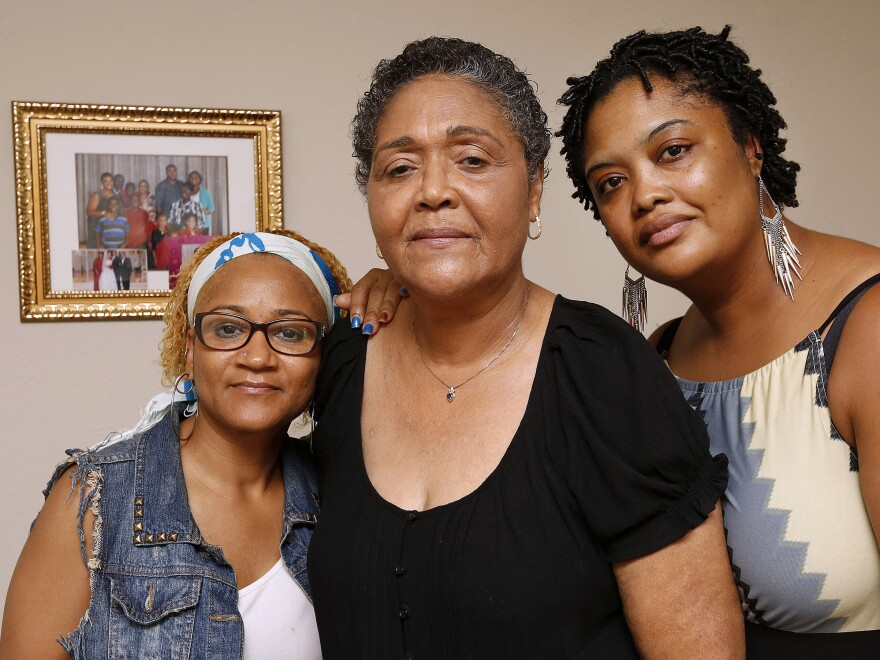 Marie Brisbane (center) and her daughters mourn the death of her husband and their father, Dr. Samuel Brisbane. He was the first Liberian doctor to die in the country's Ebola outbreak.