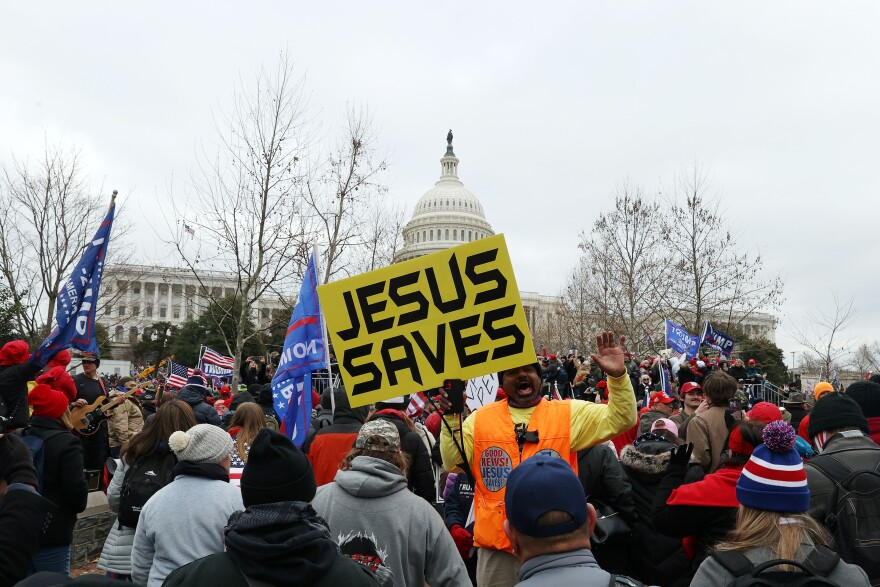 A yellow banner that reads JESUS SAVES stands out in the pro-Trump mob outside the U.S. Capitol Building on Wednesday.