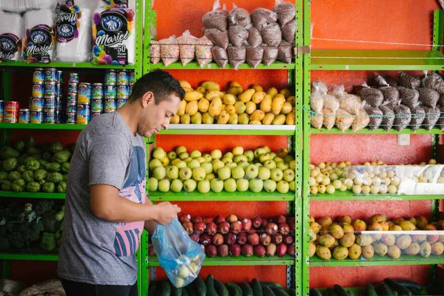 Olivas-Bejarano shops for fruit at a market in León this month. His Spanish has improved in the nearly two years he has lived in Mexico, but his American accent is noticeable among a large bilingual community.