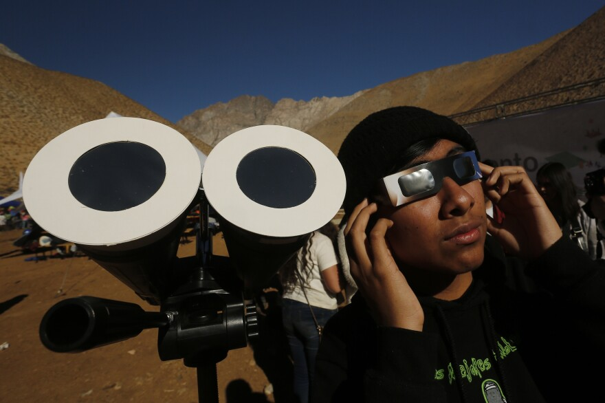 A young Chilean in Paiguano watches the sky with eclipse glasses prior to the total solar eclipse.