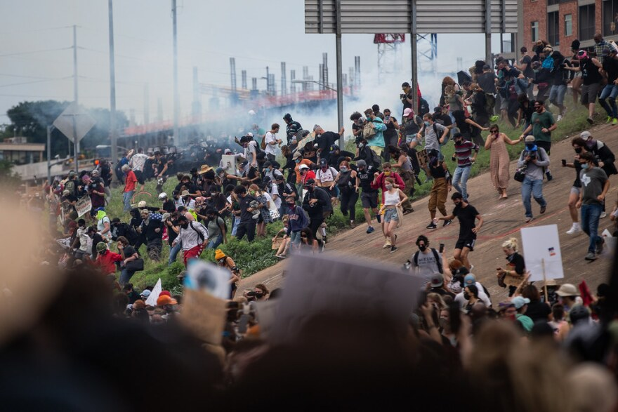 Protesters run down the ramp from I-35 after police deploy tear gas.