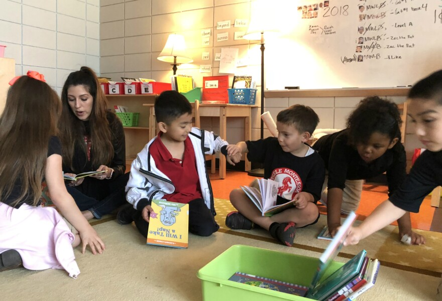 A teacher sits and reads with her students at Steele Montessori Academy in southeast San Antonio in March 2018.