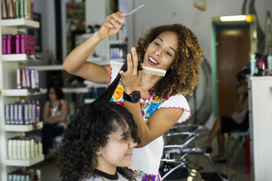 """Gerlin Santos cuts Lisney Santiago's hair at Laura Om Studio in San Juan, Puerto Rico, on Saturday. Santos left her curls natural four years ago and is the only one in her family who quit straightening her hair. For Santiago, 21, leaving her curls has given confidence. """"It even gives me more security in myself; it makes me unique. I like it,"""" Santiago says."""