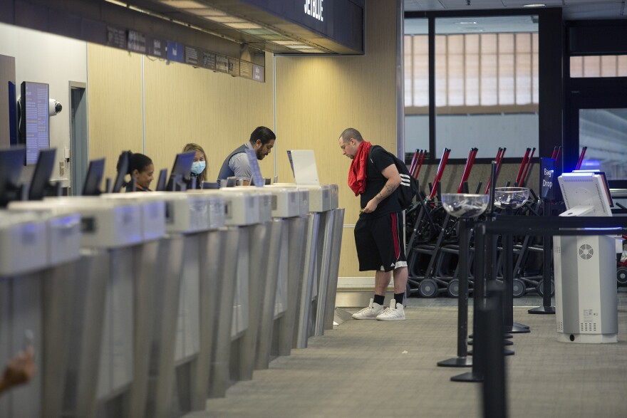 A man stands at the ticket counter of JetBlue while his luggage is checked by two airline employees wearing masks.