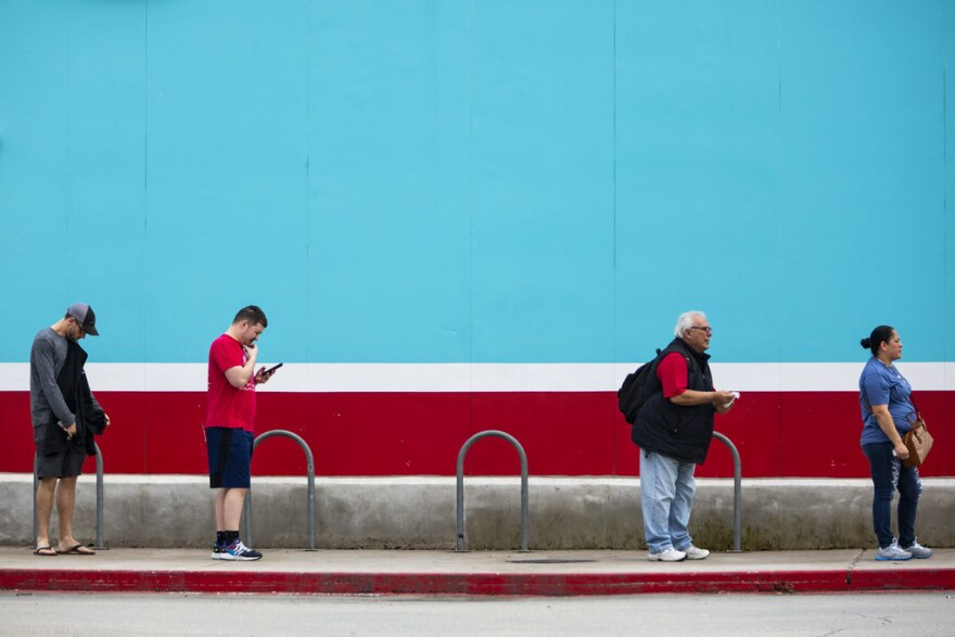 Shoppers practice social distancing while waiting to go in the H-E-B in South Austin on Monday.