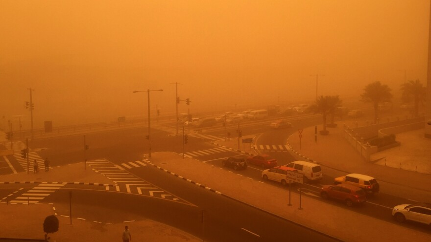 Cars are seen driving Thursday amid a sandstorm that engulfed the city of Dubai, United Arab Emirates.