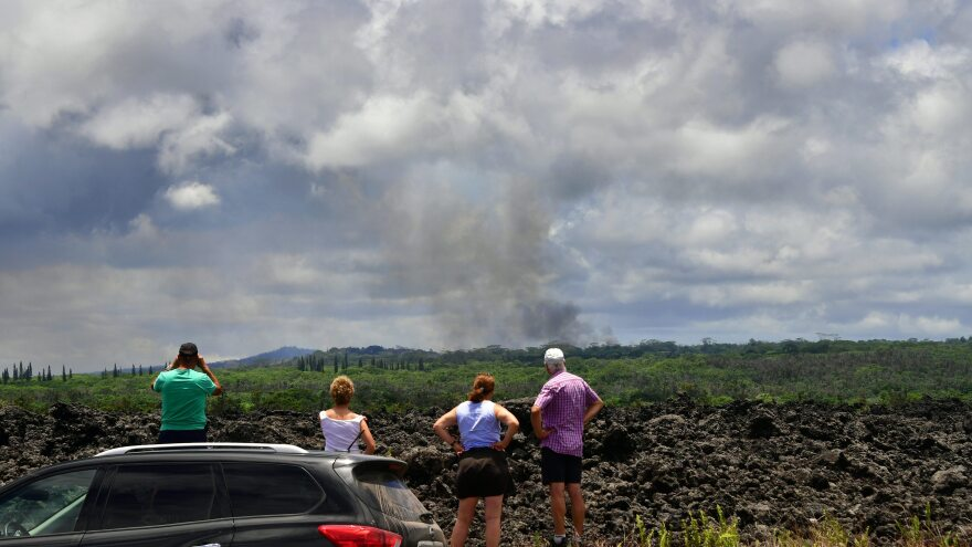 People stop on the side of the road to view a plume of smoke rising over Leilani Estates on Sunday.