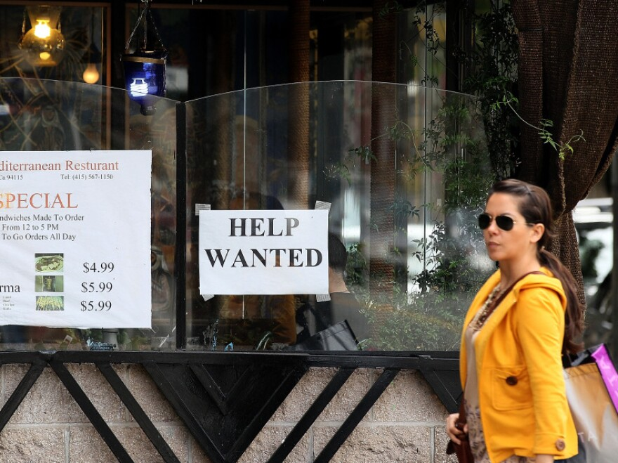"""A woman walks by a """"Help Wanted"""" sign taped to the window of a restaurant in San Francisco. Some employers are refusing to consider hiring anyone who doesn't already have a job, leading to increased scrutiny by the EEOC."""
