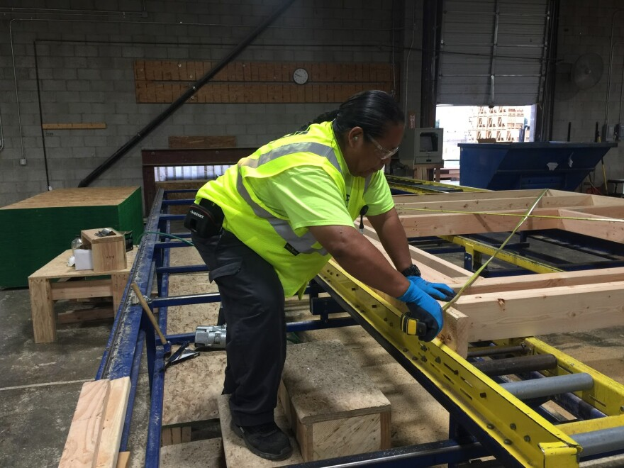 Yazzie works on building frames in a warehouse.