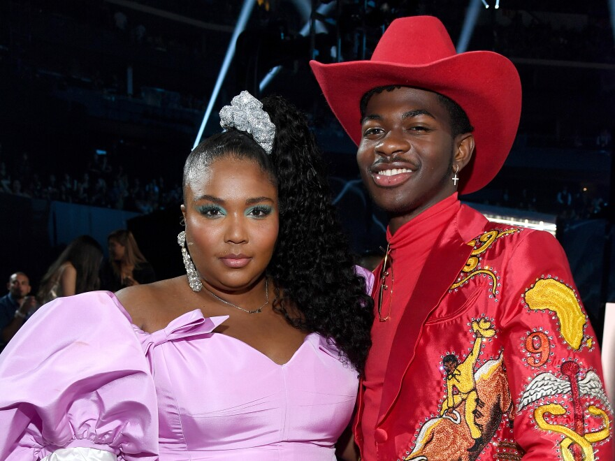 Lizzo, in a bejeweled scrunchie, poses with Lil Nas X at the 2019 MTV Video Music Awards.