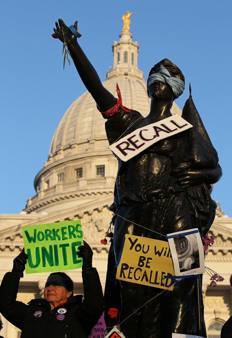A sign to recall Wisconsin Gov. Scott Walker hangs on a statue in front of the Wisconsin State Capitol in Madison last March. The recall petition drive began in November, and Democrats will turn in signatures Tuesday.