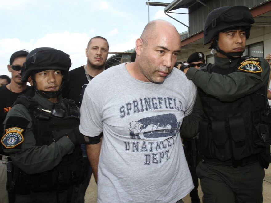 Joseph Manuel Hunter (center) is escorted by Thai police commandos to Police Aviation Division after being arrested, in Bangkok on Thursday.