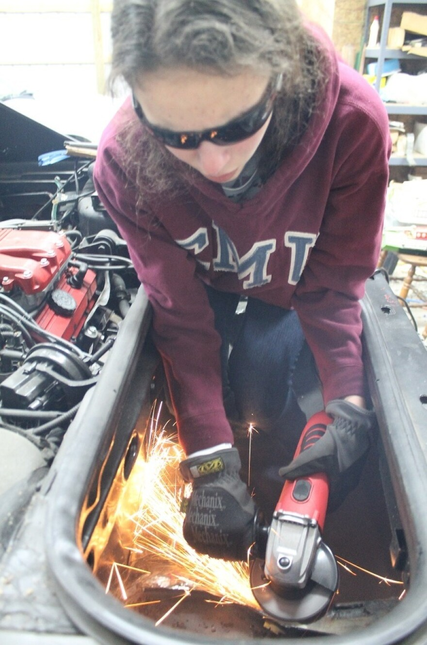 Kathryn DiMaria using her grinder to cut a hole in the trunk of her Pontiac Fiero.