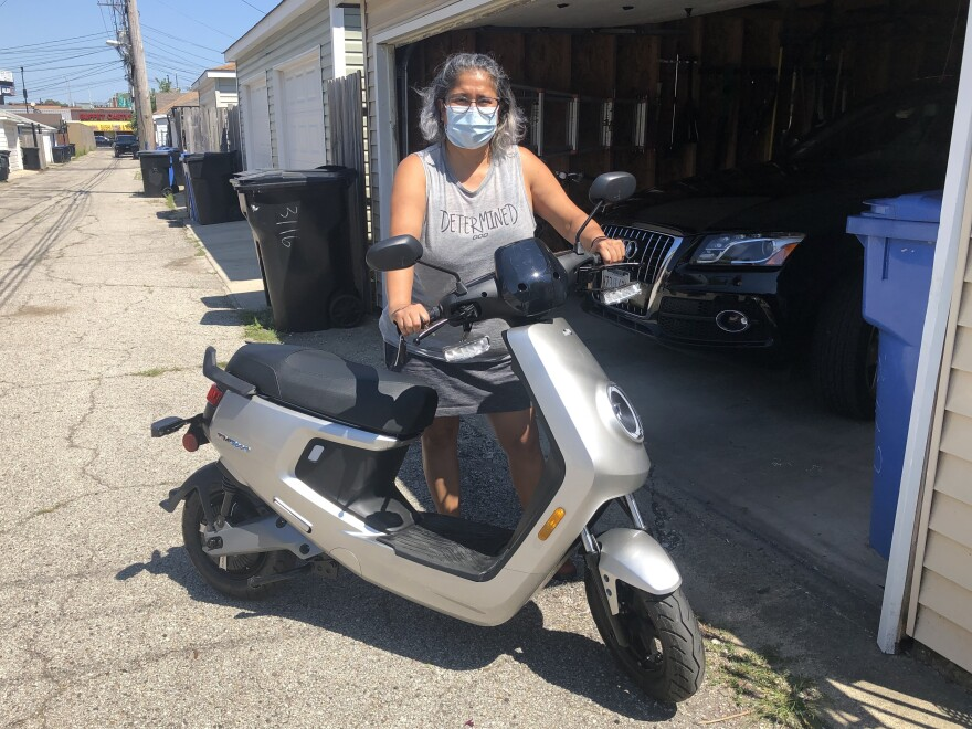 Magali Olson shows her new electric scooter, which she bought a week ago so she doesn't have to commute on the train.