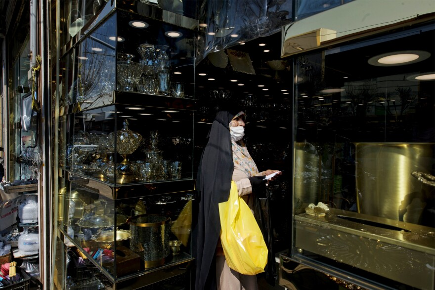 A woman wears a mask while shopping from a crystal shop in Shoosh Bazaar.