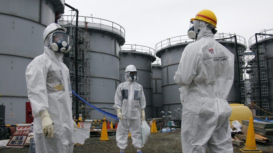 A Tokyo Electric Power Company official (center) stands with journalists at the Fukushima Dai-ichi nuclear power plant in Japan on Nov. 7. Cleanup efforts at the plant remain ongoing.
