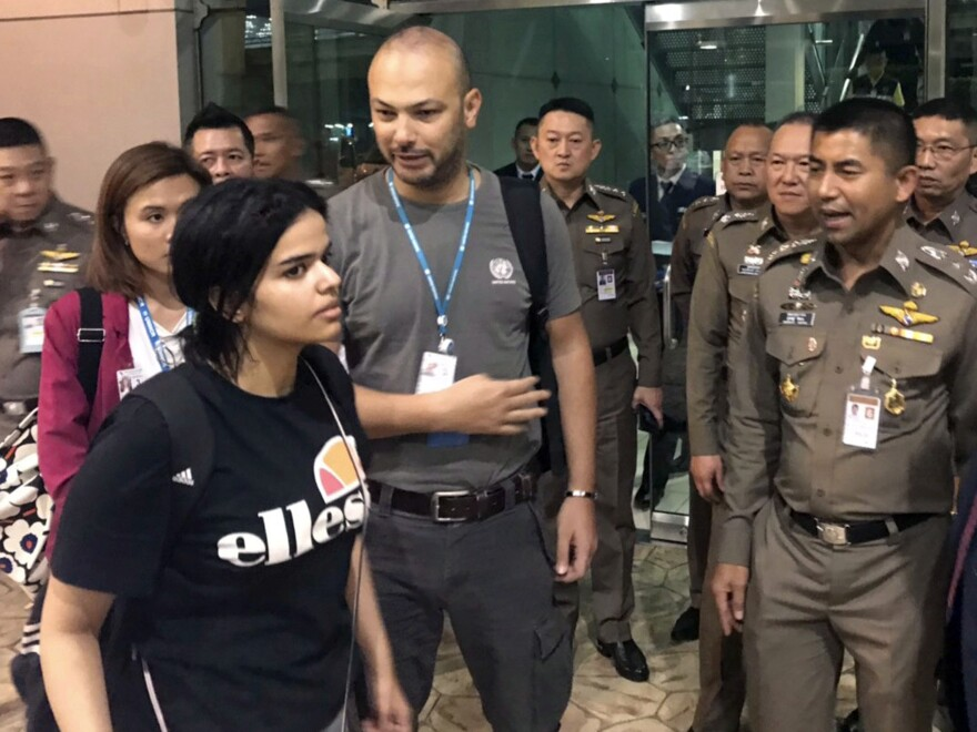 Saudi woman Rahaf Mohammed Alqunun walks by Thai Chief of Immigration Police Maj. Gen. Surachate Hakparn (right) before leaving the Suvarnabhumi Airport in Bangkok. Australia says it is considering granting refugee resettlement to the Saudi, who fled from her family, based on referral by the U.N.