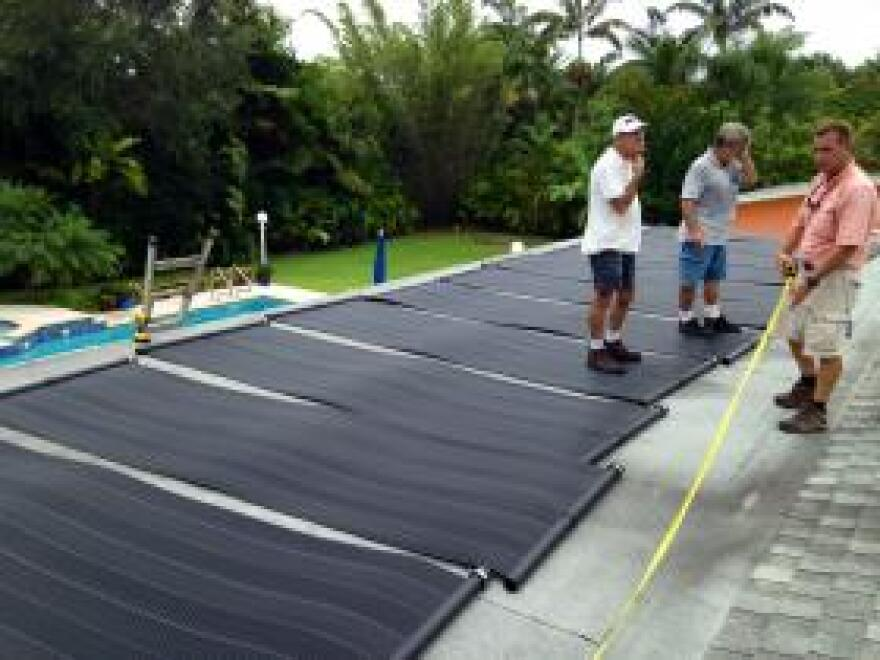 Mr. Solar team installs pool-heating panels on the roof of a Miami house.