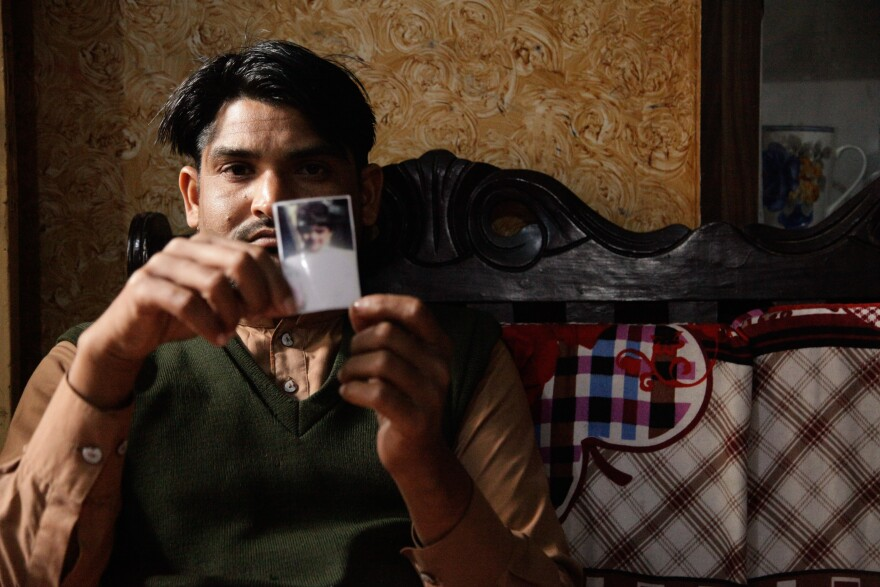 Mustafa, a barber in Kasur, holds the only image he has of his daughter, Noor-Fatima. About a year ago, he sent the 6-year-old to buy milk. She was found the next day, raped and killed, her body dumped in a construction site.