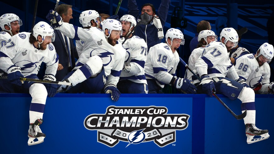 Tampa Bay Lightning players climb over a sign saying Stanley Cup Champions