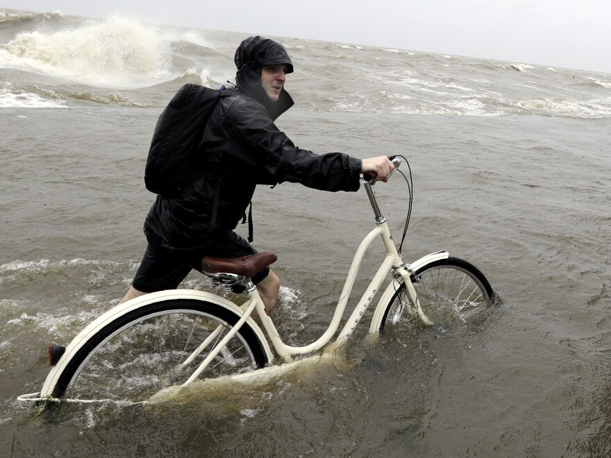 Tyler Holland guides his bike through the water as winds from Tropical Storm Barry push water from Lake Pontchartrain over the seawall Saturday.