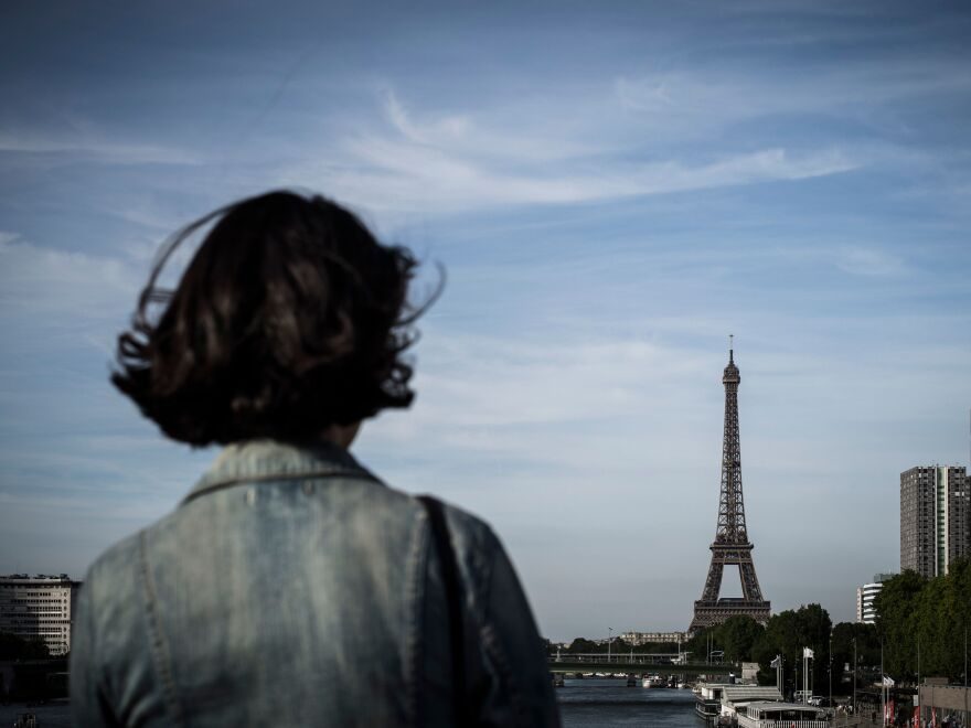 A woman stands on a bridge in front of the Eiffel tower in Paris on June 24, 2018. (Photo by Philippe LOPEZ / AFP) (Photo credit should read PHILIPPE LOPEZ/AFP/Getty Images)