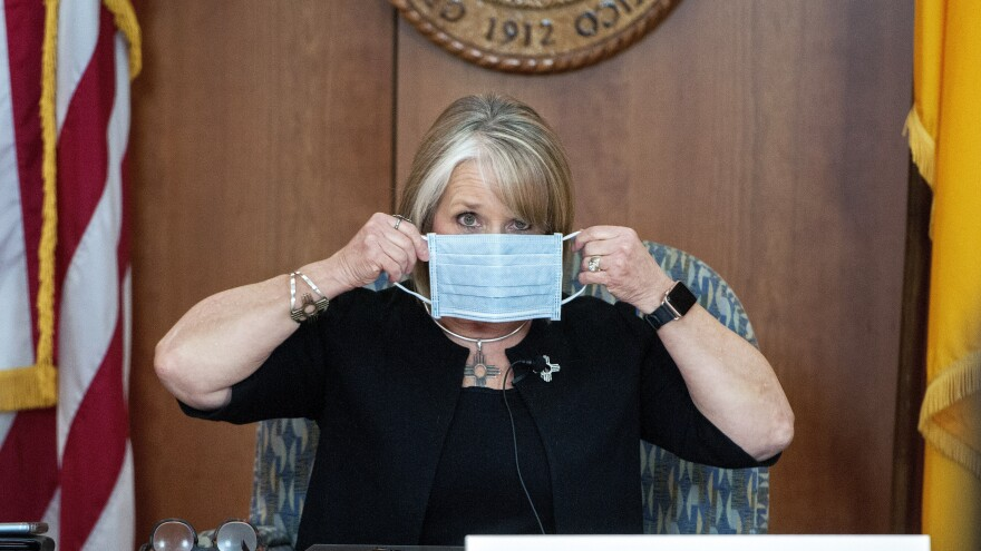 New Mexico Gov. Michelle Lujan Grisham puts on her face mask in April when not speaking during an update on the COVID-19 outbreak in the state.