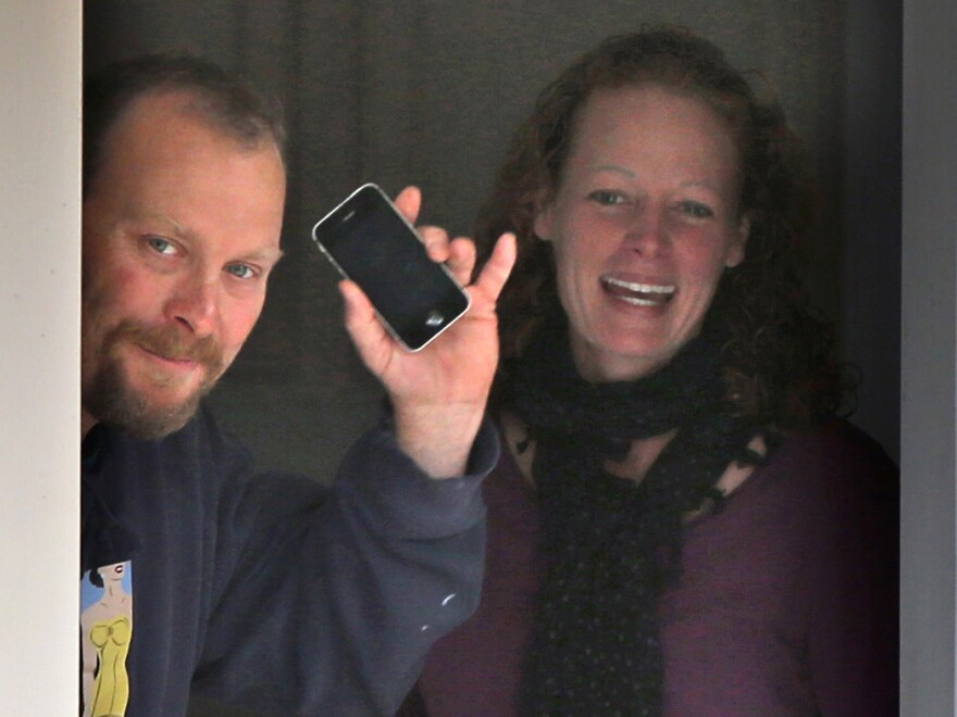 Nurse Kaci Hickox and her boyfriend, Ted Wilbur, take delivery of a pizza at their home in Fort Kent, Maine, on Thursday. A judge has ruled that the state cannot compel Hickox to remain in isolation if she's not showing signs of Ebola infection.